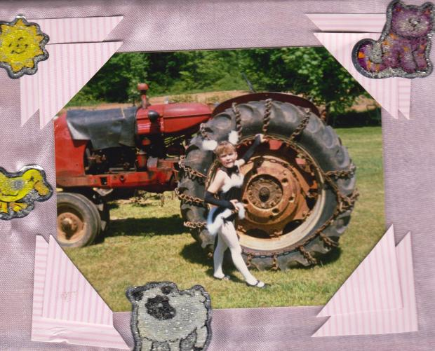 My little sister Sue in front of Pap's tractor.